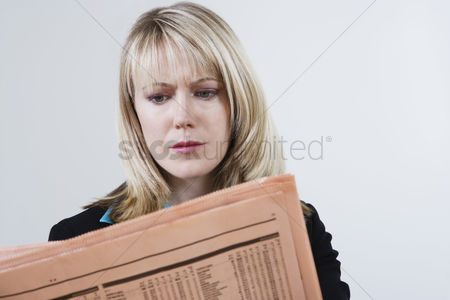 Worry : Businesswoman reading stock listings in newspaper