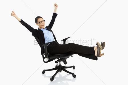 Business suit : Businesswoman resting on a chair  cheering