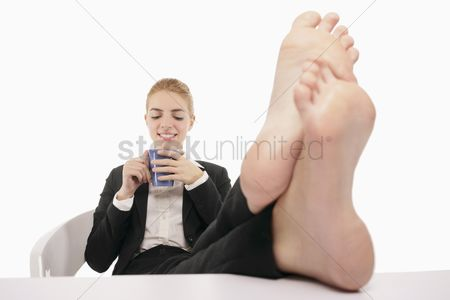 aba442a74b42ab 1851540 Legs businesswoman   Businesswoman resting with her legs up on a  table while drinking coffee