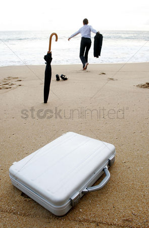 Relaxing : Businesswoman running to the sea leaving her things behind