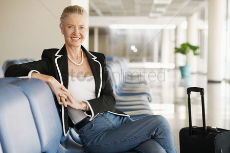 Smiling : Businesswoman sitting at airport lounge