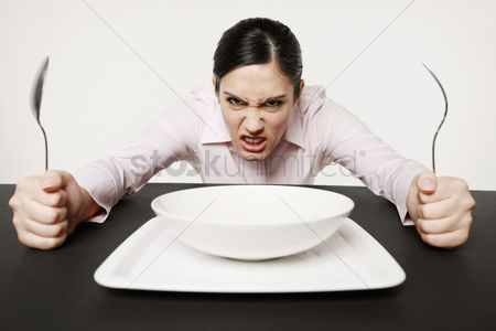 Bowl : Businesswoman sitting at table looking angry