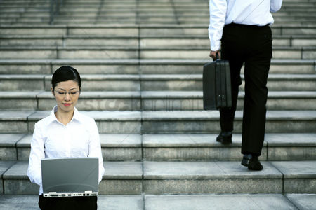 Staircase : Businesswoman sitting at the staircase using laptop