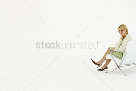 Satisfaction : Businesswoman sitting in chair on white background portrait