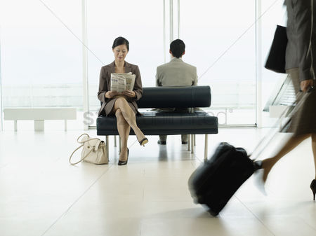 Knowledge : Businesswoman sitting on bench in airport reading newspaper
