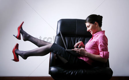 Comfort : Businesswoman sitting on the chair playing with laptop