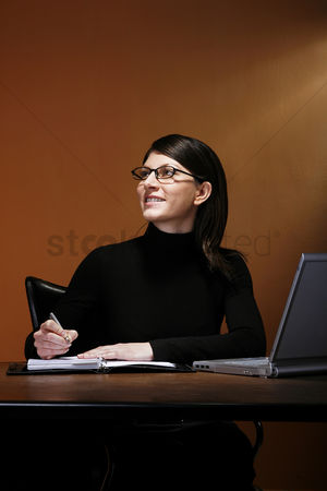 Thought : Businesswoman smiling while writing her organizer