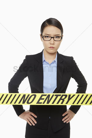 Instruction : Businesswoman standing behind a no entry sign