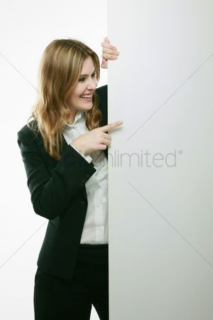 Blank : Businesswoman standing behind blank placard
