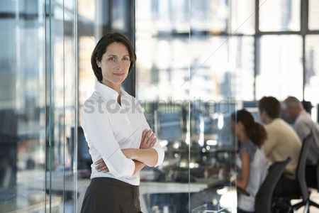 People : Businesswoman standing in office with group of office workers in background