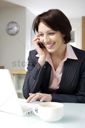 Cell phone : Businesswoman talking on the phone while using laptop