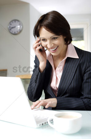 Cellular phone : Businesswoman talking on the phone while using laptop