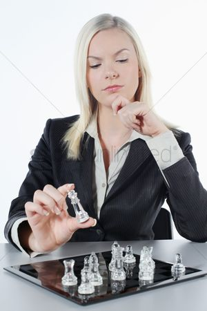 British ethnicity : Businesswoman thinking while holding chess piece
