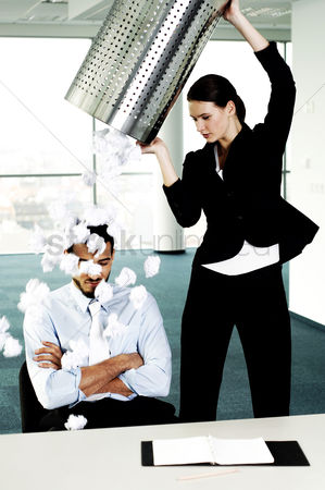 Fury : Businesswoman throwing a dustbin of crumpled papers on her colleague