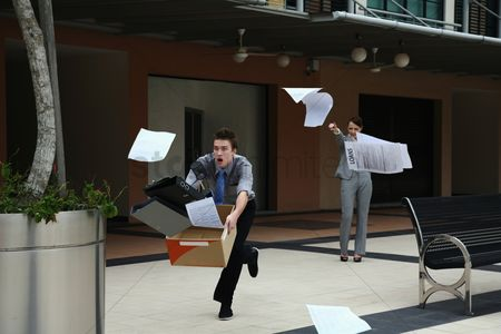 Ignorance : Businesswoman throwing papers  businessman catching them