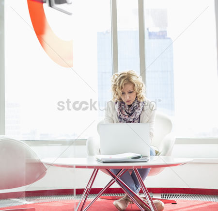 Three quarter length : Businesswoman using laptop in creative office