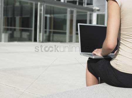 Women : Businesswoman using laptop outdoors