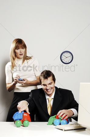 Wondering : Businesswoman using palmtop while her colleague is playing with toy cars