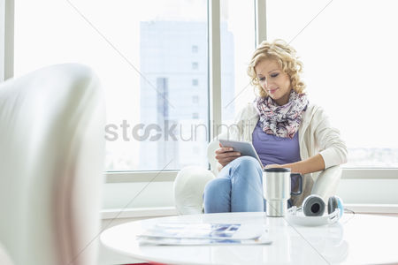 Internet : Businesswoman using tablet pc at creative office lobby