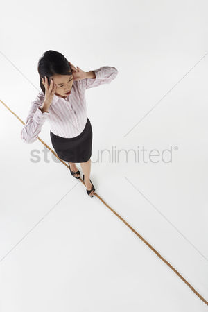 Rope : Businesswoman walking on a tightrope  stressed