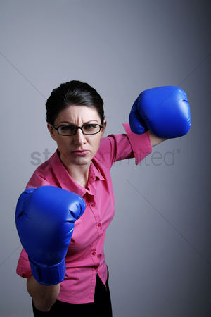 Strong : Businesswoman wearing boxing gloves