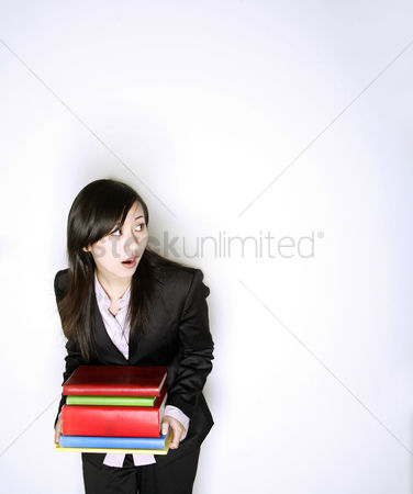 Wondering : Businesswoman with a stack of books looking up in shock