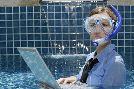 Diving : Businesswoman with diving mask using laptop in swimming pool