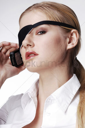Composed : Businesswoman with eye patch talking on the cell phone