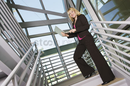 Posed : Businesswoman with laptop on stairs