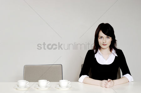 Smiling : Businesswoman with three coffee cups beside her