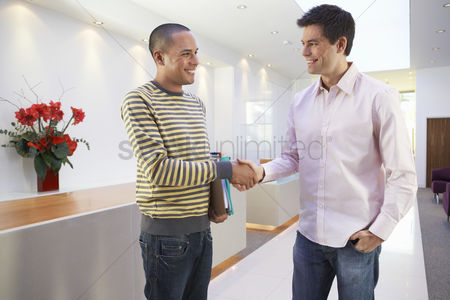 Two people : Casually dressed businessmen smiling shaking hands in office