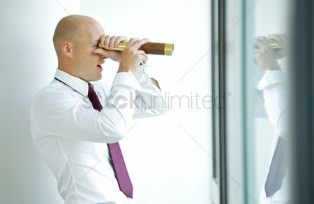 Bald : Caucasian businessman spying using telescope thru office window