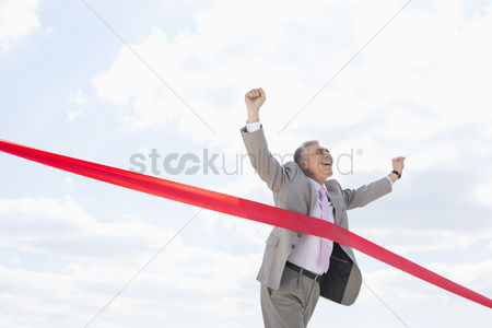 Celebrating : Cheerful businessman crossing finish line against sky