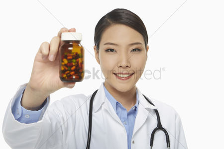 Medication : Cheerful medical personnel holding up a bottle of pills