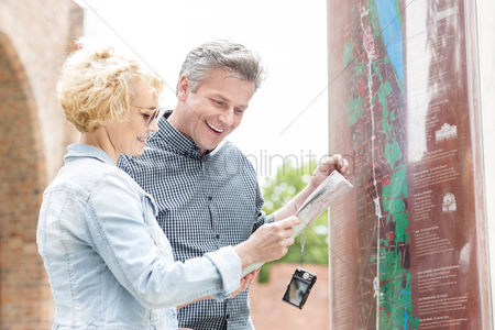 On the road : Cheerful middle-aged couple reading map in city