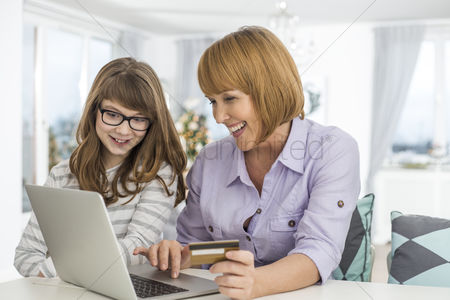 Daughter : Cheerful mother and daughter shopping online at home during christmas