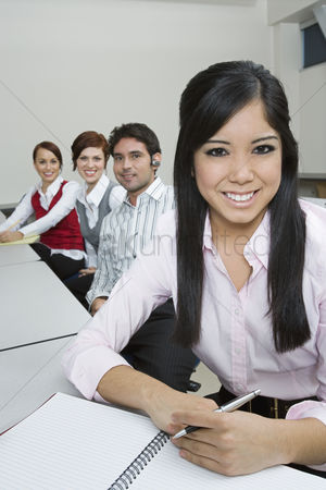 Notepad : Cheerful multi racial group of business people sitting at desk