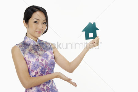 Lunar new year : Cheerful woman holding up a paper house