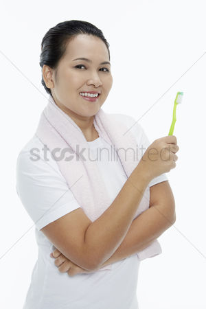 Tooth brush : Cheerful woman holding up a tooth brush