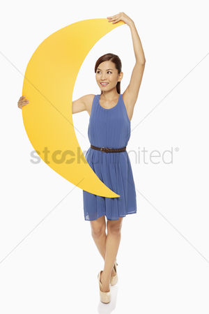 Dance : Cheerful woman holding up a yellow crescent moon