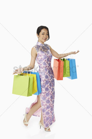 Lunar new year : Cheerful woman in traditional clothing carrying colorful paper bags