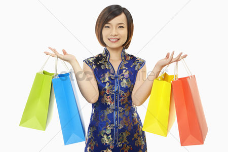 Lunar new year : Cheerful woman in traditional clothing carrying paper bags