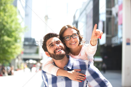 Arm raised : Cheerful woman pointing away while enjoying piggyback ride on man in city