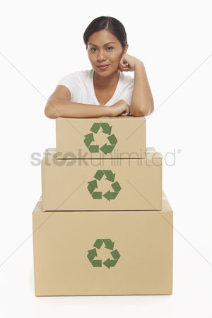 Bidayuh ethnicity : Cheerful woman resting her arms on a stack of cardboard boxes