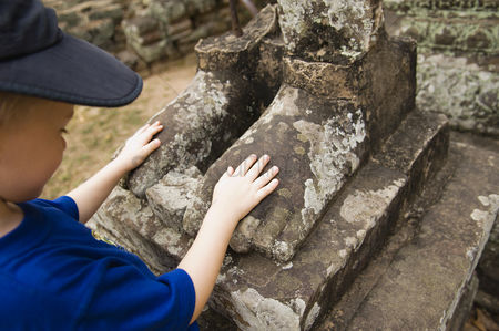 Sculpture : Child looking at feet of ancient statue