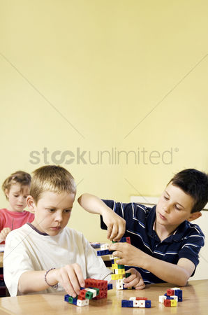 Friends : Children assembling plastic blocks
