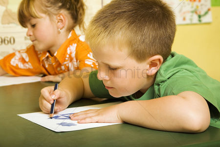 Young boy : Children colouring in the classroom