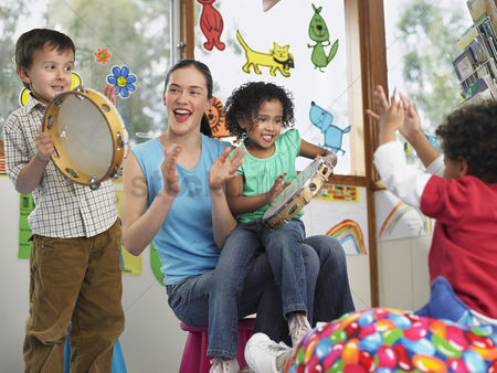 School : Children with teacher playing music in classroom