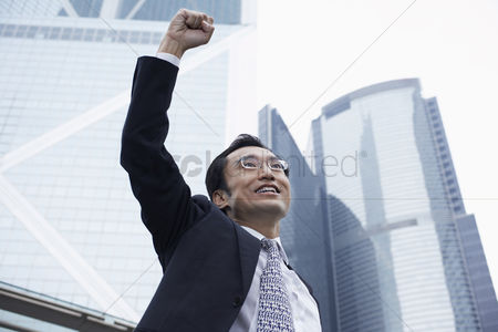 China : China hong kong business man with risen fist low angle view