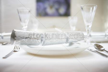 Interior : Christmas cracker on place setting on table close up